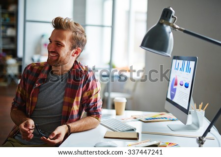 Casual young businessman sitting at his workplace - stock photo