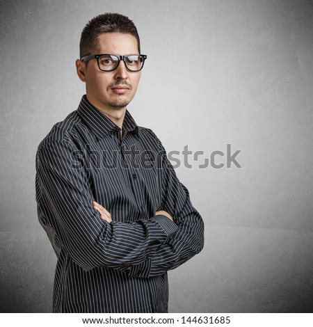 Casual young businessman standing arms crossed - stock photo
