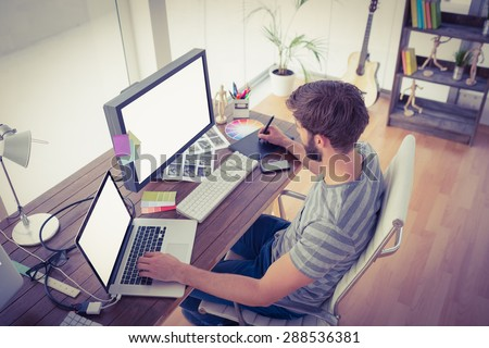 Casual young businessman using computers in office - stock photo