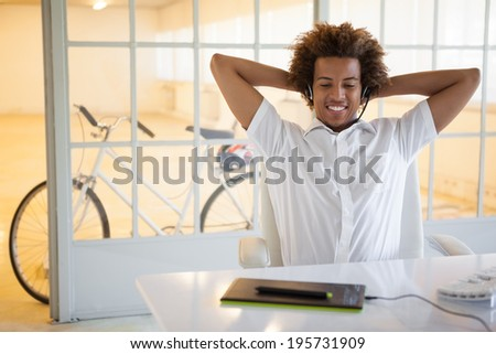Casual young businessman using digitizer and headset at desk in his office
