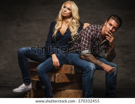 Casual young couple sitting on wooden box.