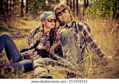 Casual young couple sitting together on a grass on a sunny day. - stock photo