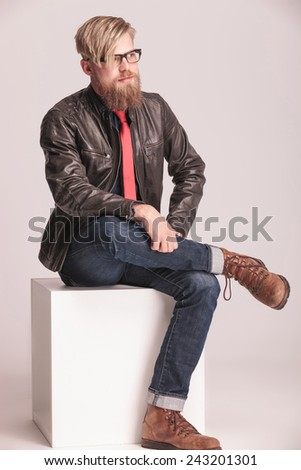 Casual young fashion man sitting on a white cube holding his legs crossed, looking away from the camera. - stock photo