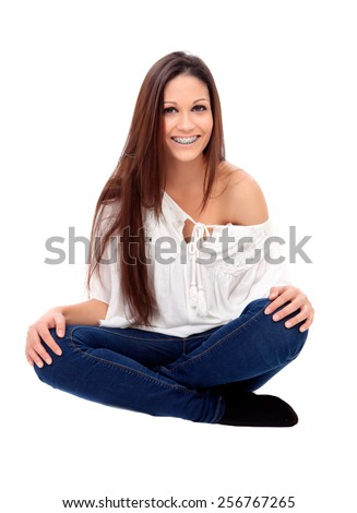 Casual young girl with brackets sitting isolated on a white background - stock photo