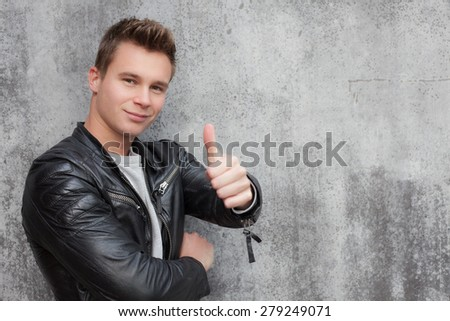 Casual young guy showing thumbs up - stock photo