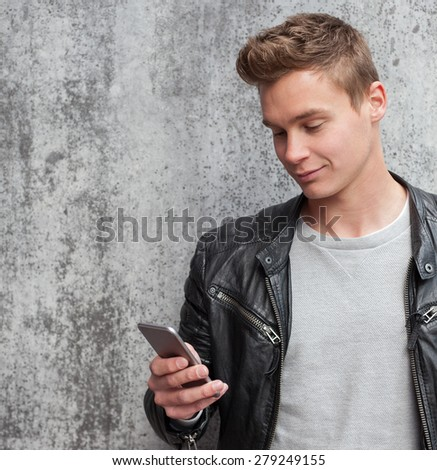 Casual young guy using smart phone - stock photo