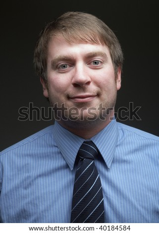 Casual young handsome businessman portrait on dark background - stock photo