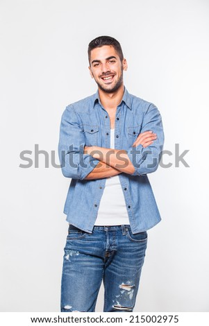 Casual young handsome man in jeans looking at camera - stock photo