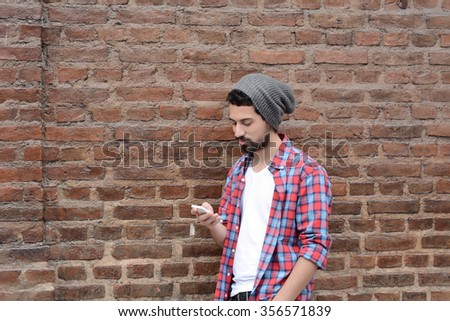 Casual young latin man using a smartphone. - stock photo