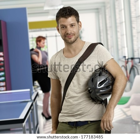 Casual young man at office arriving to work by bicycle. - stock photo