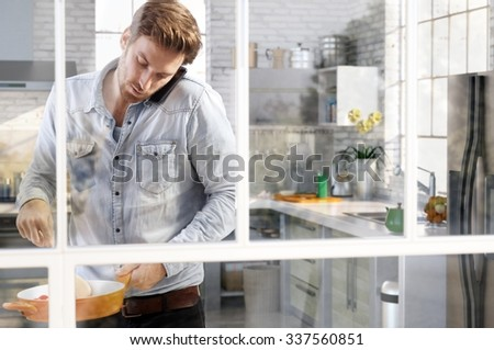 Casual young man cooking in kitchen chatting on phone, through the window view.