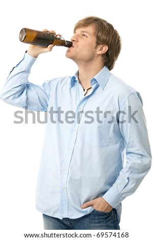 Casual young man drinking bottle of beer. Isolated on white.? - stock photo