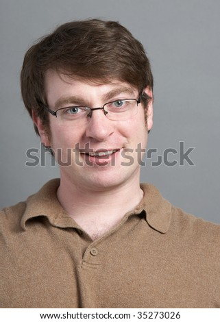 Casual young man headshot on grey background - stock photo