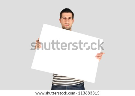 Casual young man holding a banner against a grey background - stock photo