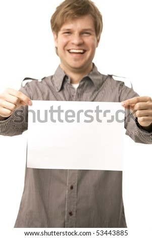 Casual young man holding blank sheet of paper, smiling. Isolated on white, selective focus on paper. - stock photo