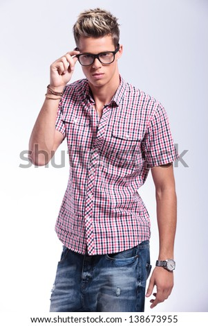 casual young man holding his hand on his glasses and fixing them while looking at the camera. on gray background
