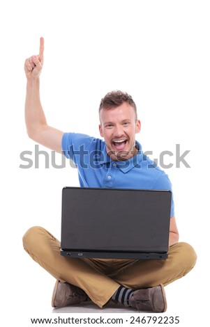casual young man holding his laptop while sitting on the floor with his feet crossed and pointing up with a smile on his face. on a white background