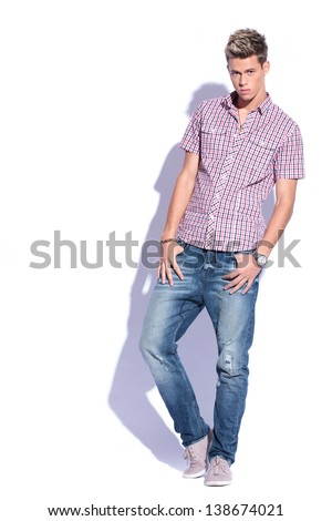 casual young man holding his thumbs in his pockets and looking at the camera. on white background with hard shadow