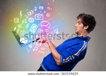 Casual young man holding laptop with colorful hand drawn multimedia symbols
