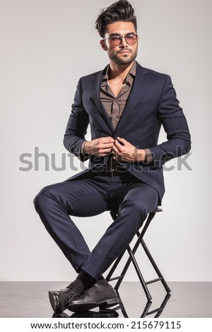 Casual young man in leather jacket pulling his sunglasses, sitting on the floor, looking at the camera - stock photo