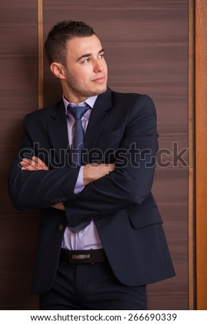 Casual Young Man in suit Standing With His Arm Crossed over wood wall - stock photo