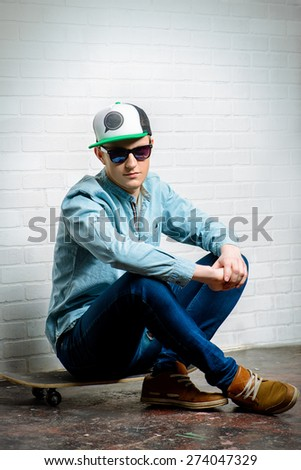 Casual young man in sunglasses sitting on his skateboard by the brick wall.  - stock photo