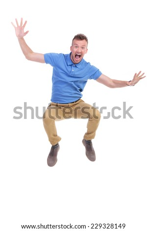 casual young man jumping in the air and screaming with his arms wide open. on white background - stock photo