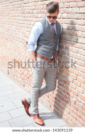 casual young man leaning on a brick wall and looking down while holding his hands in his pockets - stock photo
