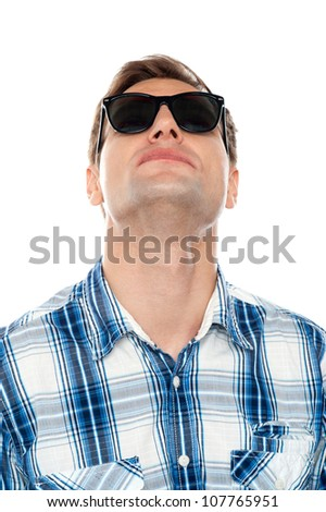 Casual young man looking upwards wearing sunglasses - stock photo