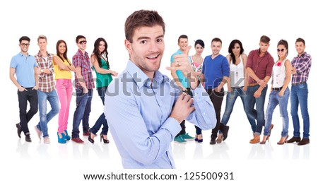 casual young man making the call me hand gesture in front of a large group of casual fashion people