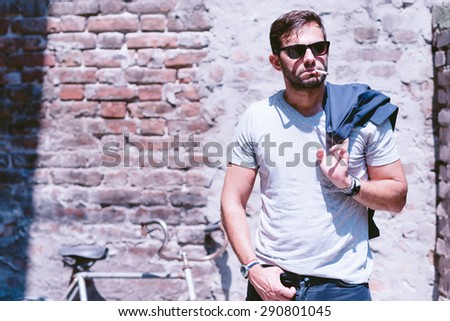 Casual young man outdoors,l with a cigarette