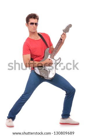 casual young man playing his electric guitar and looking at the camera. isolated on a white background