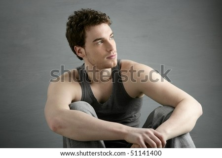 casual young man portrait sit over gray grunge background - stock photo