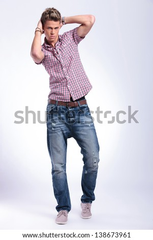 casual young man posing with his hands at the back his head while looking at the camera. on gray background
