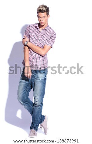 casual young man posing with legs crossed. on white background with hard shadow - stock photo