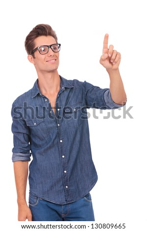casual young man pushing an imaginary button and looking at it with a smile on his face. isolated on a white background - stock photo