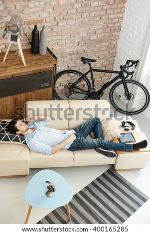 Casual young man relaxing at home, lying on sofa, talking on mobilephone. - stock photo