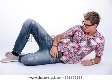 casual young man relaxing on the floor, sitting on his elbow and looking away from the camera. on  gray background