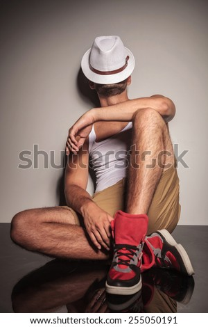 Casual young man resting on the floor with his hat on his face. - stock photo