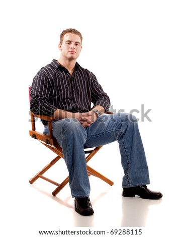 Casual young man seated in directors chair. - stock photo