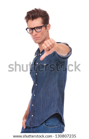 casual young man showing thumbs down sign and holding a hand in his pocket while looking at the camera with a serious look on his face. isolated on a white background - stock photo