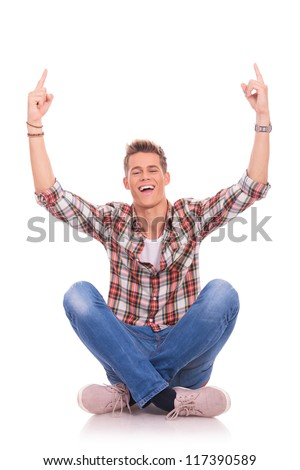 casual young man sitting cross legged on the floor and pointing excited upwards with both hands. isolated on white