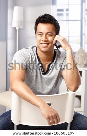 Casual young man sitting on chair, talking on mobilephone, smiling, looking away. - stock photo