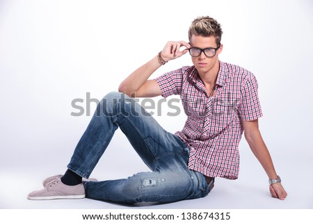 casual young man sitting on the floor and adjusting his eyeglasses while looking at the camera with serious expression. on background - stock photo
