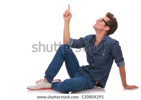 casual young man sitting on the floor and pointing and looking upwards while smiling. isolated on white - stock photo