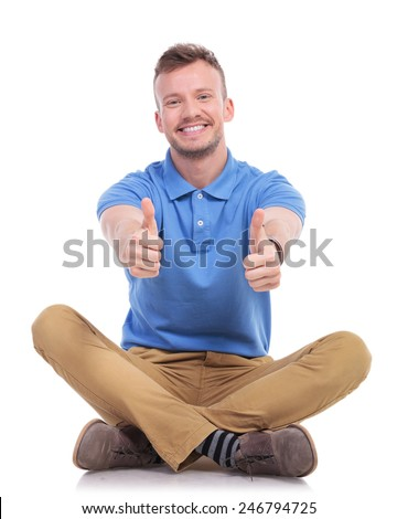 casual young man sitting on the floor with his legs crossed and showing thumbs up gesture with both hands while smiling for the camera. isolated on white - stock photo