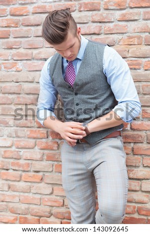 casual young man standing by a brick wall and looking at his watch, checking the time - stock photo