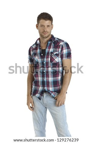 Casual young man standing in jeans and shirt, looking at camera. - stock photo