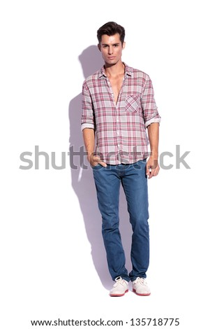 casual young man standing with a hand in his pocket and looking at the camera. isolated on a white background - stock photo