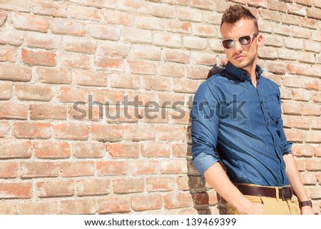 casual young man standing with a hand in his pocket by a brick wall - stock photo